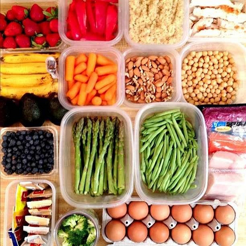 Various foods assorted into containers and cartons such as strawberries, peppers, eggs, bananas, blueberries, almonds, green beans, chicken, carrots, chickpeas, broccoli, and couscous.