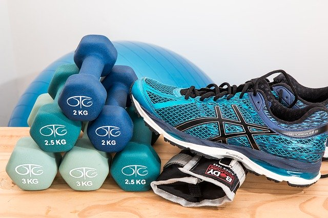 Dumbbells in pyramid with a shoe lying against it. Exercise ball is in the background.