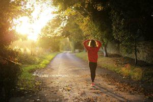 Woman walking on park trail as the sun rises.
