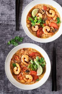 Soups with shrimp, vegetables, and a lime.