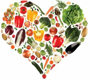 Vegetables and fruits arranged in the shape of a heart.