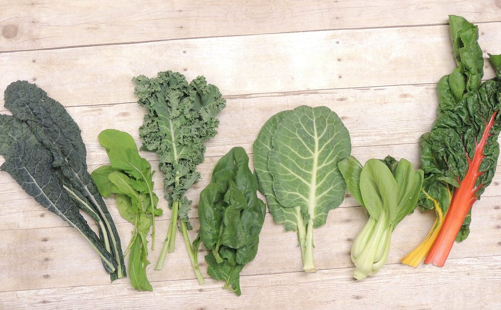 Kale, arugula, spinach, collard, bok choy, and chard on a wooden table.
